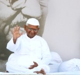 """28 Aug 2011, New Delhi, Delhi, India --- Veteran social activist Anna Hazare waves to the supporters, in front of a photograph of Mohandas Karamchand Gandhi, on the thirteenth day of Hazare's fast at Ramlila grounds in New Delhi, India on Sunday, August 28, 2011. Hazare broke his fast after India's Parliament expressed nonbinding support for a series of anti-corruption proposals on Saturday in the hopes that would be enough to persuade the reform activist to end his hunger strike. Hazare, a 74-year -old self styled Gandhian is demanding a bill for creating an autonomous, powerful anti-corruption agency, known as """"Lokpal"""", a campaign that has drawn support from the middle class Indians and seen millions of them protest against the Government. In April, Mr. Hazare gained national attention when he undertook a hunger strike for a Lokpal ? a tactic that forced officials to invite him and his allies to negot --- Image by © Amit Bhargava/Corbis"""
