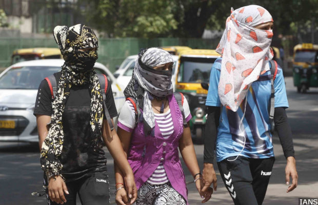 New Delhi: People cover their faces to protect himself from the scorching heat on a hot sunny day, in New Delhi on May 22, 2018. (Photo: IANS)