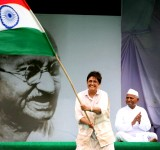 """19 Aug 2011, New Delhi, Delhi, India --- Veteran social activist Anna Hazare, right, sits on the forth day of his fast, in front of the photograph of Mohandas Karamchand Gandhi, at the Ramlila grounds in New Delhi, India on Friday, August 19, 2011. Hazare, a 74-year -old self styled Gandhian, is fasting until death to demand a bill for creating an autonomous, powerful anti-corruption agency, known as """"Lokpal"""", a campaign that has drawn support from the middle class Indians and seen millions of them protest against the Government. Hazare was arrested by the Delhi Police before he could start his agitation on August 16, 2011. In April 2011, Mr. Hazare gained national attention when he undertook a hunger strike for a Lokpal ? a tactic that forced officials to invite him and his allies to negotiations over legislation to create such an agency. A bill is pending in Parliament, but Mr. Hazare has argued that --- Image by © Amit Bhargava/Corbis"""
