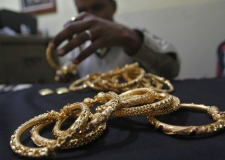 Goldsmith holds finished gold bangles at workshop in Kolkata