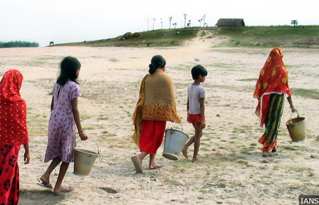 Women carry empty buckets to fetch water from river as water crisis prevails in Malda district of West Bengal on May 14, 2014. (Photo: IANS)
